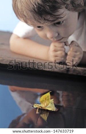 leaf ship in children hand, focus on ship - stock photo