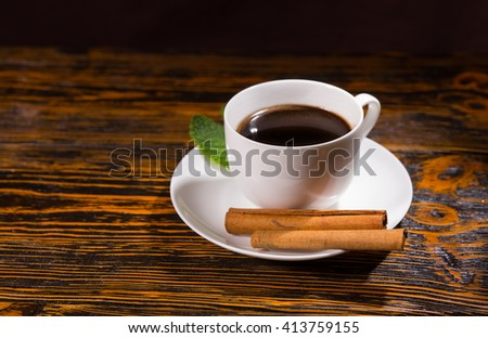 Leaf with black tea in cup and saucer beside pair of cinnamon sticks over wooden table