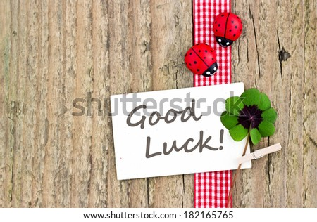 Leafed clover, ladybugs and card on wooden board/good luck/english - stock photo
