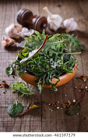 Leafy green mix of kale, spinach, baby beetroot leaves in a wooden bowl over rustic wooden background. Selective focus, shallow depth of field