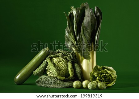 Leafy vegetables against green background - stock photo