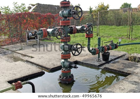 Leaking oil from pipes. Ground pollution - stock photo