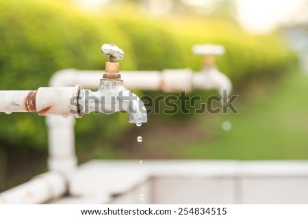 Leaking waste water dripping from faucet. - stock photo