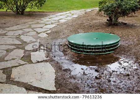 Leaks around the locking lids of a septic system's tanks - stock photo