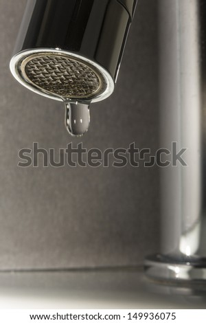 Leaky Tap/ a chrome bathroom tap with a faulty washer causing a leak or drip  - stock photo