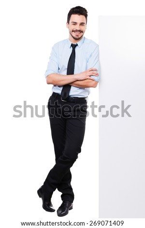 Leaning at the copy space. Full length of handsome young man in shirt and tie leaning at the copy space and keeping arms crossed while standing against white background - stock photo