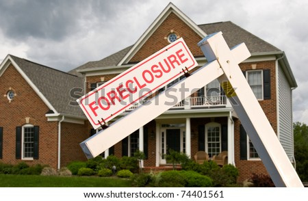 Leaning foreclosure sign in front of a modern single family home on a cloudy cold day - stock photo