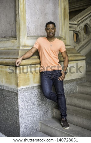 Leaning on a column, a young handsome black guy is standing on a staircase and smilingly looking at you./Portrait of Young Black Guy - stock photo
