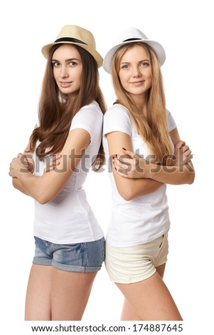 Leaning on each other. Two happy girls in straw hats and white tshirts standing back to back, against white background - stock photo
