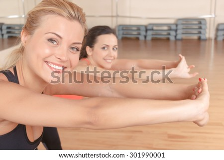 Leaning to purpose. Pretty blond-haired woman with her friend doing stretching exercises by leaning forward.