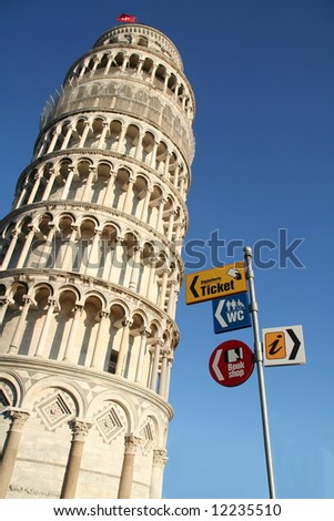 Leaning tower of Pisa with tourist signs - stock photo