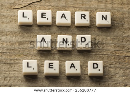 Learn and Lead text on a wooden background