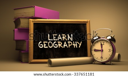 Learn Geography - Chalkboard with Hand Drawn Inspirational Quote, Stack of Books, Alarm Clock and Rolls of Paper on Blurred Background. Toned Image. - stock photo