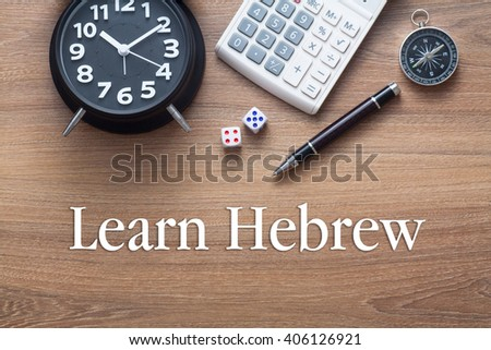 Learn Hebrew written on wooden table with clock,dice,calculator pen and compass - stock photo