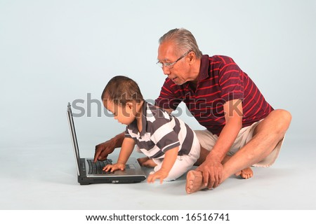Learn how to use a laptop computer with grandpa - stock photo