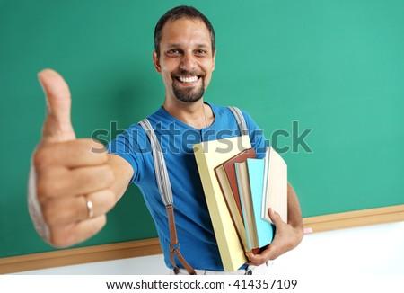 Learn it's cool! Joyful teacher showing thumbs up. Photo adult teacher near blackboard, education concept - stock photo