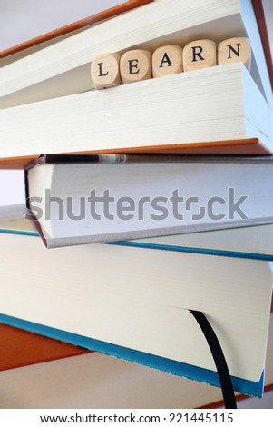 Learn message written in wooden blocks between pages of a book, stack of books, symbol, concept - stock photo