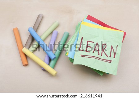 Learn Note on Adhesive Green Paper with Chalks - stock photo