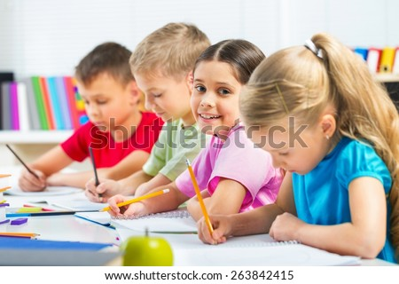 Learn. Portrait of cute schoolboy drawing at workplace among his classmates - stock photo