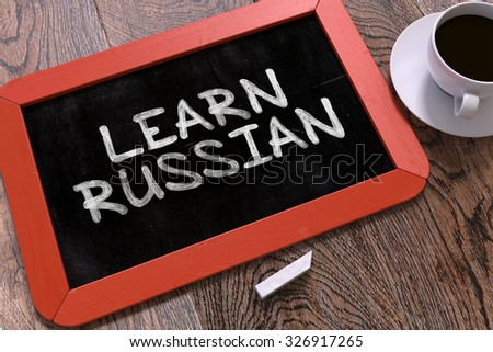 Learn Russian Handwritten by white Chalk on a Blackboard. Composition with Small Red Chalkboard and Cup of Coffee. Top View. - stock photo