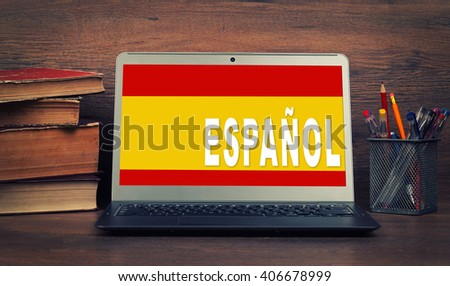 Learn spanish concept. Laptop, books and school supplies. Education - stock photo
