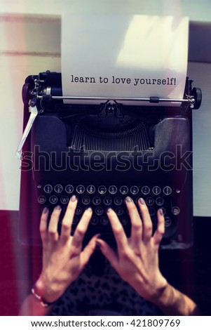 Learn to love yourself message on a white background against womans hand typing on typewriter - stock photo