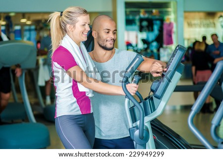 Learning a new trainer in the gym. Young smiling fitness instructor demonstrates how to use the simulator - stock photo