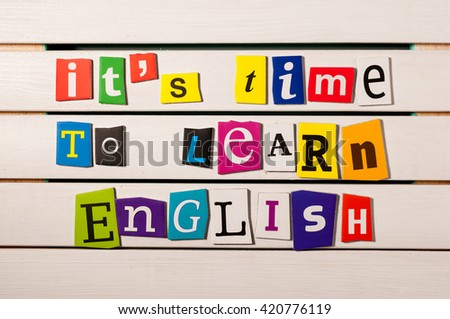 learning english concept. it's time to learn English - written with color magazine letter clippings on wooden board