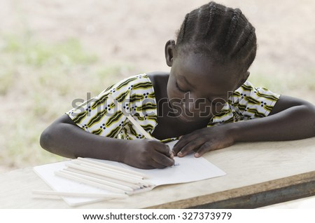 Learning for a Better Future: African Black Girl Studying School. Young black girl drawing in her exercise book sitting in her desk at school. Education for African children symbol background. - stock photo