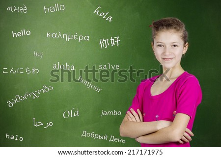 Learning foreign languages. Portrait confident teenager girl student standing by chalkboard with word hello written in different foreign languages. Education concept, international communication - stock photo