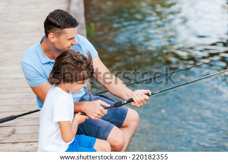 Learning from the professional. Top view of father and son fishing while sitting on riverbank  - stock photo