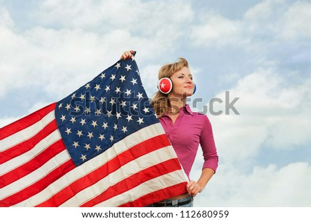 Learning language � American English (blond young woman with american flag, outdoor) - stock photo