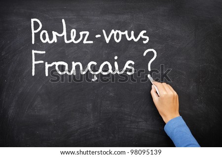 Learning language - French. Learning French language concept of teacher or student writing parlez-vous francais (do you speak French) on blackboard / chalkboard. - stock photo