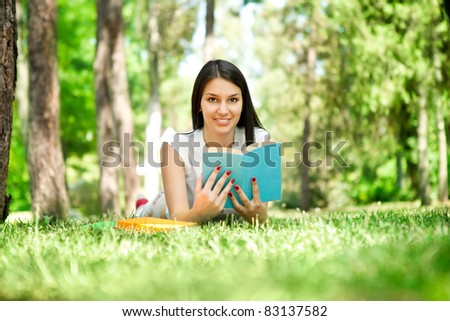 learning outdoor, girl with book in park