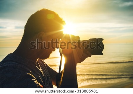 Learning Photography at Sunset. Photographer Practicing Taking Pictures.  - stock photo