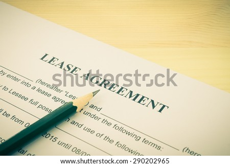Lease Agreement Contract Document and Pencil Bottom Left Corner on Wood Table in Vintage Style. Legal document for business event