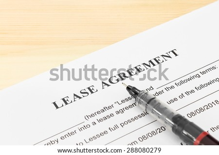 Lease agreement contract sheet and brown pen at bottom right corner on wood table background - stock photo