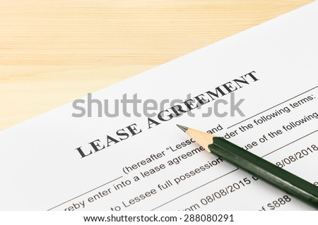 Lease agreement contract sheet and brown pencil at bottom right corner on wood table background