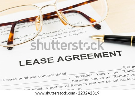 Lease agreement document with glasses and pen - stock photo