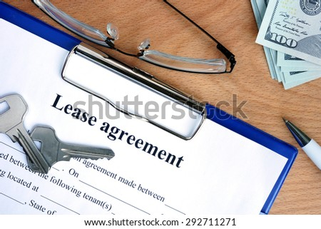 Lease agreement document with money on a wood background - stock photo