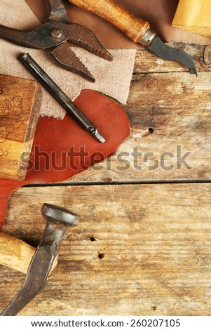 Leather and craft tools on wooden background - stock photo