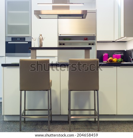 leather bar stools at work plate of modern whibte kitchen - stock photo