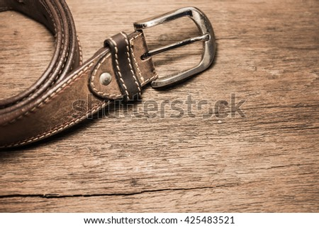 Leather belt for men on wood background. - stock photo