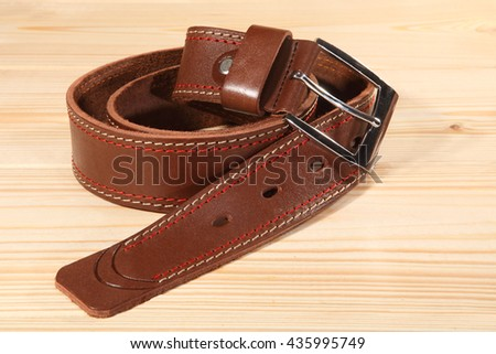 Leather belt with a metal buckle for men's trousers on the wooden background. - stock photo