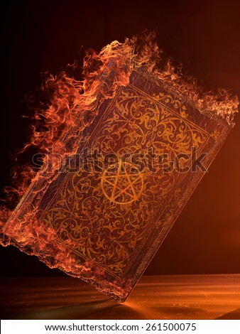 Leather Book in flames With Pentagram - stock photo