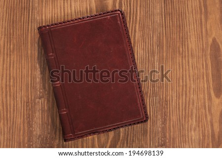 leather book on wooden board - stock photo