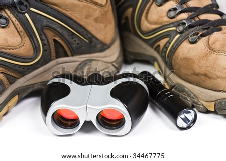 Leather boots with binoculars and flashlight - stock photo