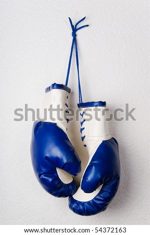 Leather boxing gloves hanging on wall. White and blue colors. Protective sports equipment, protect from injury. Sport accessories for professional sportsmen.