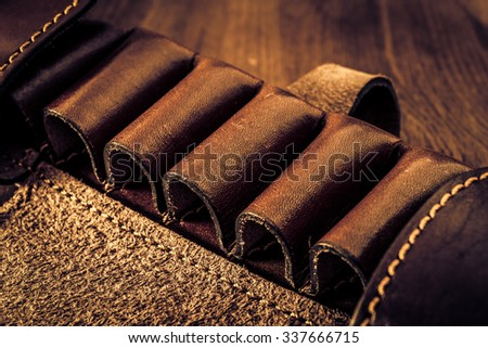Leather cartridge belt for hunting cartridges on a wooden table. Image vignetting and the yellow-blue toning - stock photo