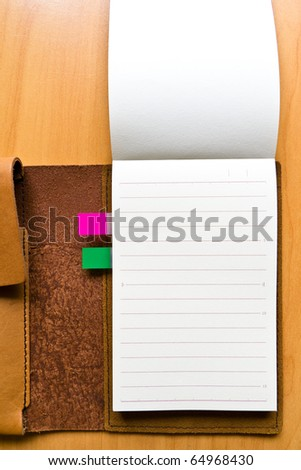 leather case notebook on wood background - stock photo